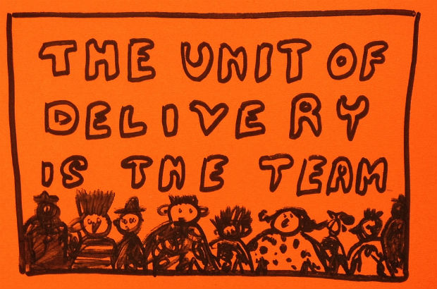 "Post it note saying ""The unit of delivery is the team"" with a cartoon drawing of a team."