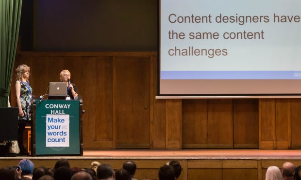 "Presenters on stage at ConCon 5 with slide saying ""Content designers have the same content challenges"""