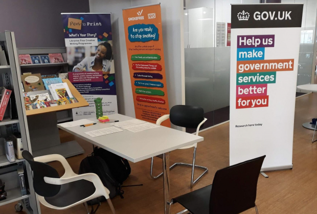 A table and chairs in a library with a big GOV.UK banner next to them