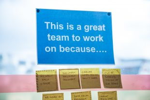 A poster that says 'This is a great team to work on because…'. Underneath the poster there are several post-it notes, each in a different person's handwriting. They say: 'Respect each other', 'Document, document, document', 'Change when things don't work', 'Clear, shared vision of our goals'.