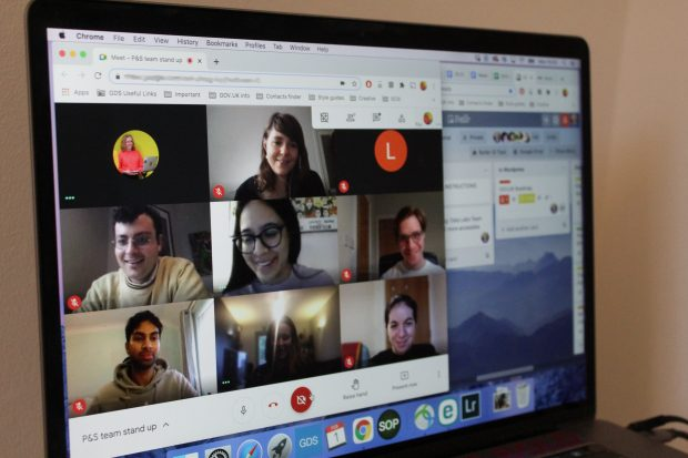 A laptop screen showing a team standup and a Trello board.