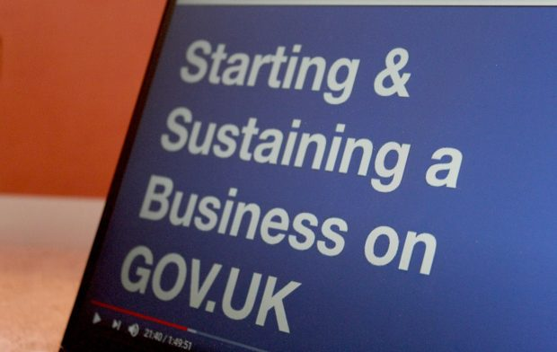 "A laptop showing a presentation slide with the words ""Starting & Sustaining a Business on GOV.UK."""