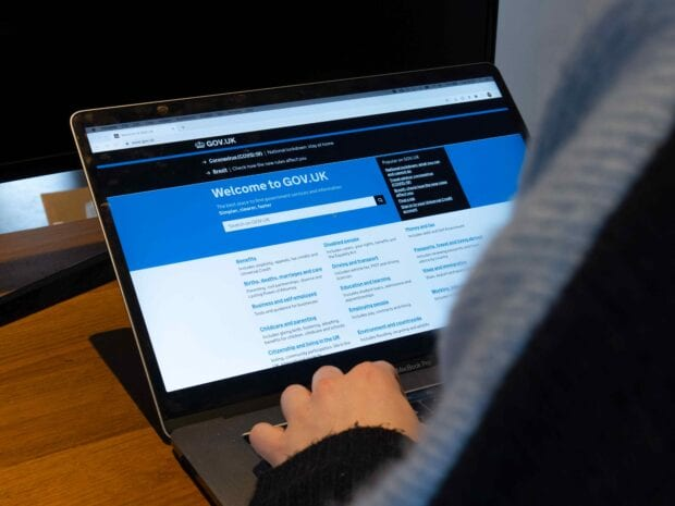 A person using a laptop with the screen displaying the GOV.UK homepage.