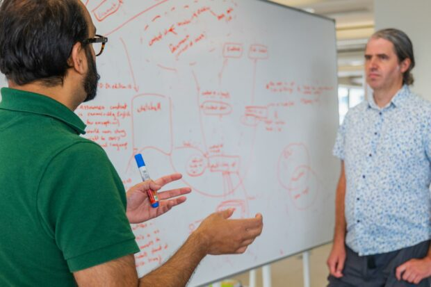 2 men standing by a whiteboard with an architecture diagram on